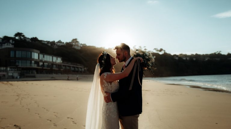 Image of a Bride and Groom taken at Carbis Bay Hotel & Estate beach in Cornwall with the Ocean Suite Wedding venue in the background of the image. The image was taken during Zoe and Nathans Wedding on 18th May 2019 at the Ocean Suite. Zoe and Nathan are a wedding couple Elastic Lounge provided a full wedding entertainment package for. The wedding package Elastic lounge Entertainment provided for Zoe and Nathan included: - Ley Adewole from the Grace Notes Gospel Wedding Singers performing with a pianist during he wedding ceremony and drinks reception. - Licence to Swing, Jazz Trio performing during the wedding breakfast - Wedding Band - Wedding DJ and Saxophone - and a wedding DJ Set This is an image on the Cornwall Wedding Entertainment website page: https://www.elasticlounge.com/wedding-entertainment-cornwall