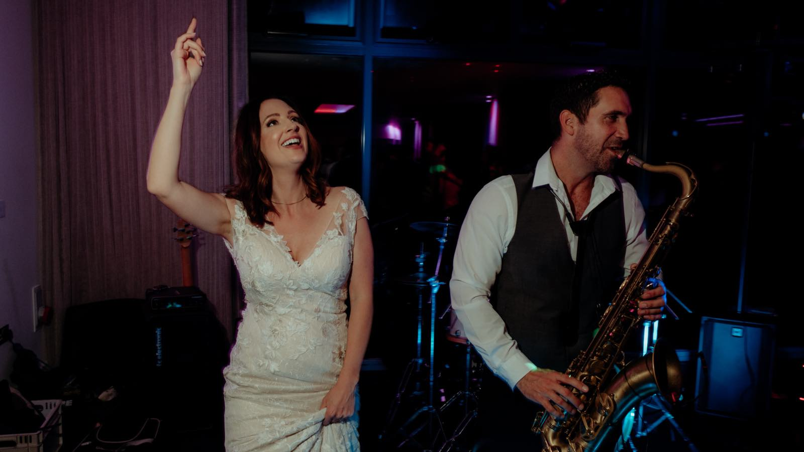 Image of a bride dancing next to a male wedding saxophonist during a wedding reception at the Ocean Suite, Carbis Bay Hotel & Estate in Cornwall. The image was taken during a Cornwall Wedding Entertainment package Elastic Lounge provided for Zoe and Nathan Kill on 18th May 2019. The entertainment being performed at the time of the photo was wedding DJ and Saxophone entertainment in Cornwall. This is a background image on the Cornwall Wedding Entertainment website page: https://www.elasticlounge.com/wedding-entertainment-cornwall and overlaying the image is a course of recent testimonials from Cornwall Wedding Entertainment supped by Elastic Lounge. One of the testimonials overlaying the image is from the wedding of Zoe Kill who is in the photo.